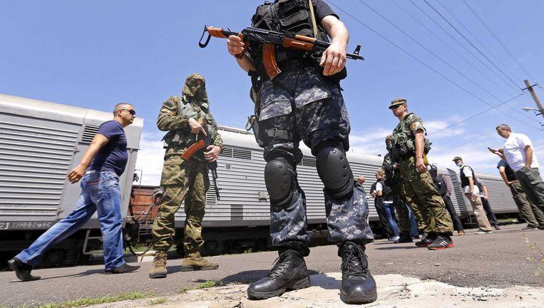 Gewapende pro-Russische rebellen bewaken een trein op het station van Torez met bijna 200 lichamen van de vliegramp. Beeld epa
