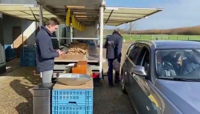 Marktkoopman Kees van der Beek bedient een klant.