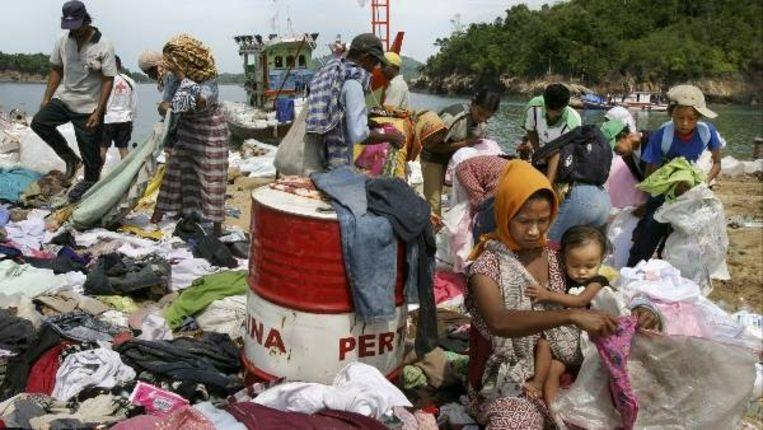 Mensen zoeken kleding uit die per schip op het strand van Calang is gebracht. Calang is zeer zwaar door de Tsunami getroffen omdat het dorp tussen twee stukken zee is ingeklemd. (Jörgen Caris, Trouw) Beeld