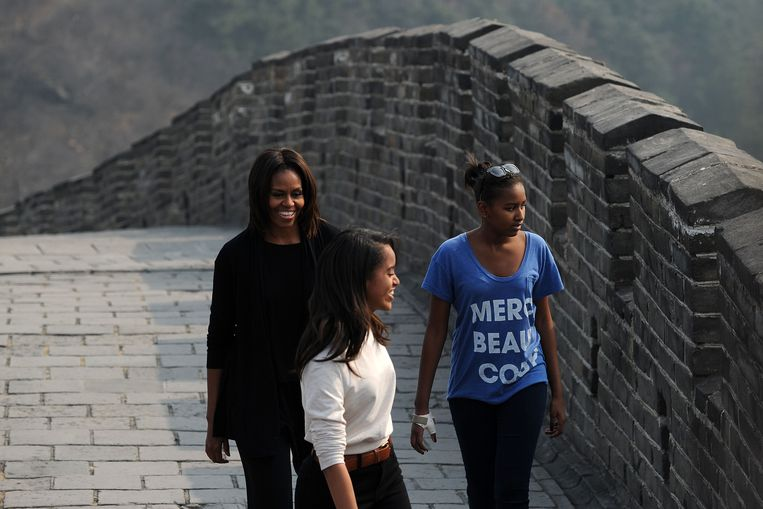US First Lady Michelle Obama (L) walks with her daughters Malia (C) and Sasha (R) during a visit to the Great Wall at Mutianyu, northeast of Beijing, on March 23, 2014.  Michelle Obama arrived in Beijing on March 20 with her mother and daughters to kick off a seven-day, three-city tour to focus on education and cultural exchange.     AFP PHOTO / WANG ZHAO Beeld AFP