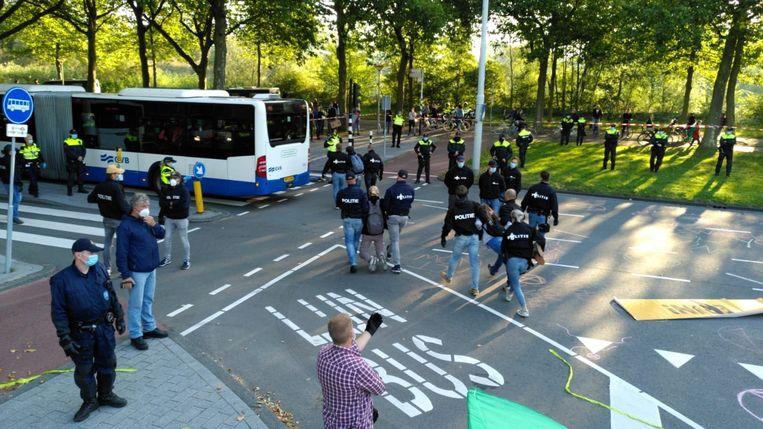 De eerste activisten worden door de politie weggehaald. Beeld Het Parool