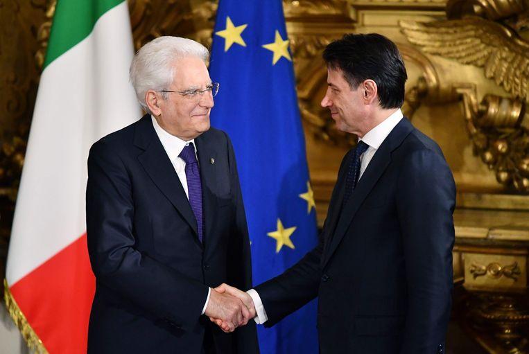 Italië's nieuwe premier Giuseppe Conte (rechts) schudt de hand van president Sergio Mattarella tijdens zijn beëdiging.  Beeld AFP