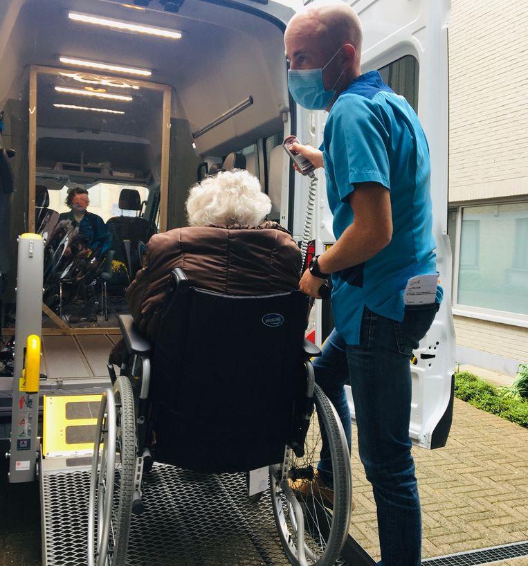 Een verpleger brengt een bejaarde naar de Babbelbus