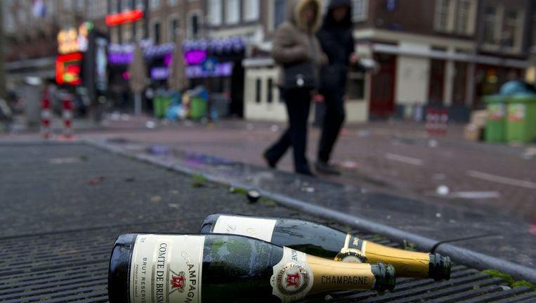 Lege flessen op de grond op het Rembrandtplein zijn de stille getuigen van oudejaarsnacht. Beeld anp