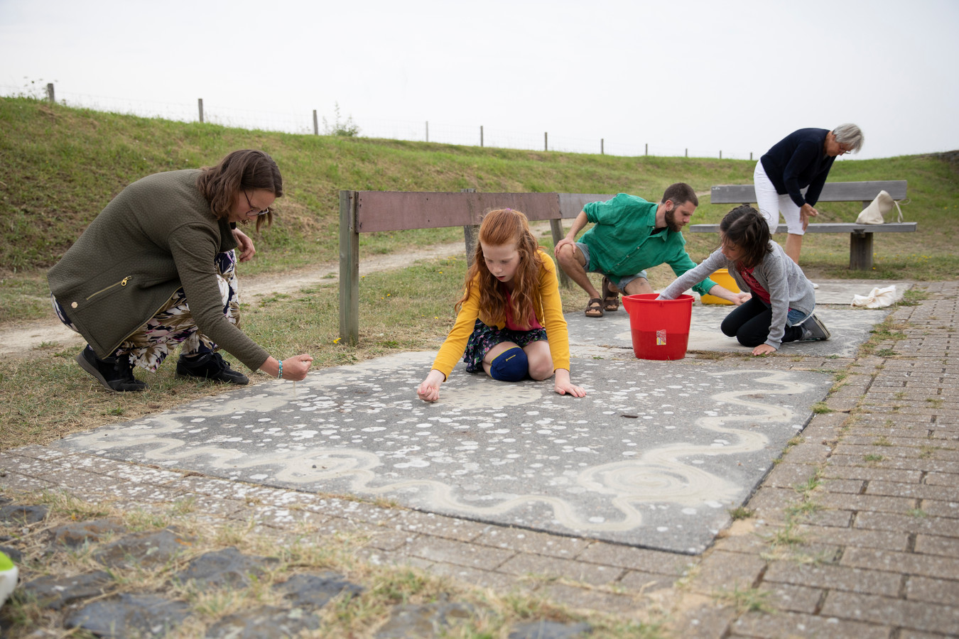 Paul Nieboer (derde van links) pleit voor de terugkeer van de traditie om een zandtapijtje te maken. Maritza Wandel (l) en haar kinderen Elin en Joni doen mee met de workshop van de kunstenaar, net als Ria Schoof (helemaal achter).