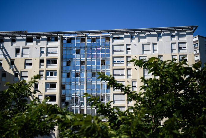 """Sur cette photo d'archive prise le 17 juillet 2021, des draps attachés ensemble et utilisés pour s'échapper sont vus se balançant des fenêtres après que trois personnes ont péri dans un incendie dans un immeuble en partie squatté, aux """"Flamants"""", un quartier défavorisé de Marseille, dans le sud de la France."""