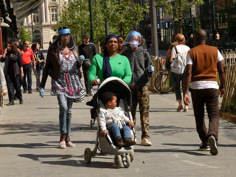 Mensen met mondmasker lopen door Brussel. Beeld Photo News