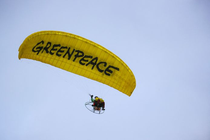 Un militant de Greenpeace se prépare à atterrir avec un parapente sur le toit du siège de la Banque centrale européenne (BCE) avant de déployer une banderole contre la politique climatique de la banque, le 10 mars 2021 à Francfort-sur-le-Main, dans l'ouest de l'Allemagne.