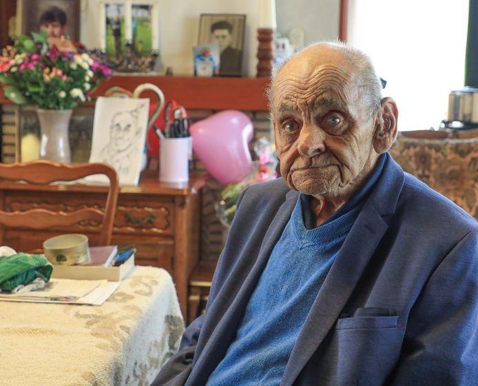De honderdjarige Piet de Hullu met zijn cadeaus op de achtergrond