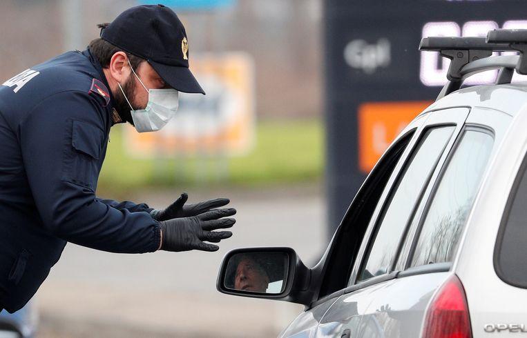 Een politieman houdt wagens tegen op de weg naar Codogno, een van de steden die in quarantaine gingen.  Beeld REUTERS