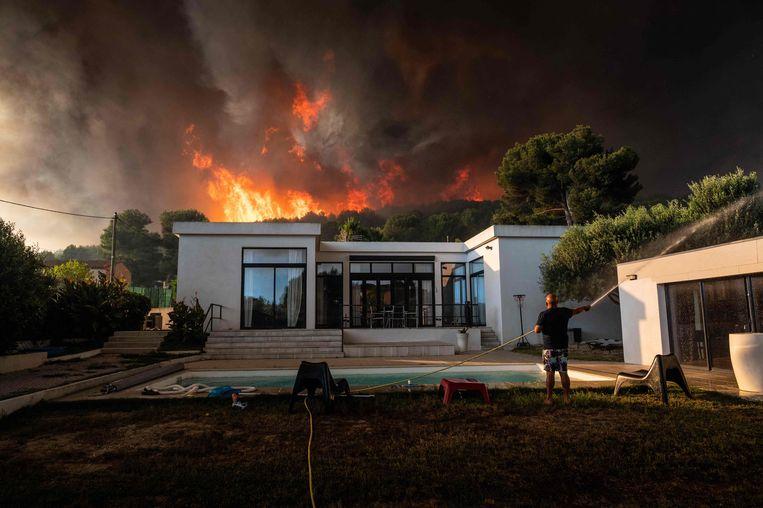 Een man gebruikt een tuinslang om zijn huis te doordrenken want de bosbrand woedt achter zijn huis.  Beeld AFP