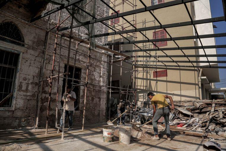 Arbeiders werken aan de renovatie van een pand in de wijk Karantina.  Beeld Reporters / DPA