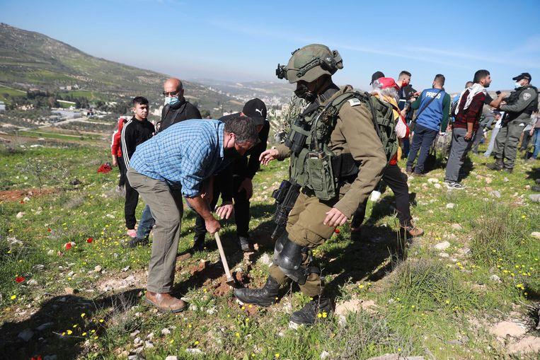 Een Israëlische soldaat weerhoudt een Palestijnse activist ervan een boom te planten in Burin, een Palestijns dorp in het Nablus-gouvernement. Beeld Anadolu Agency via Getty Images