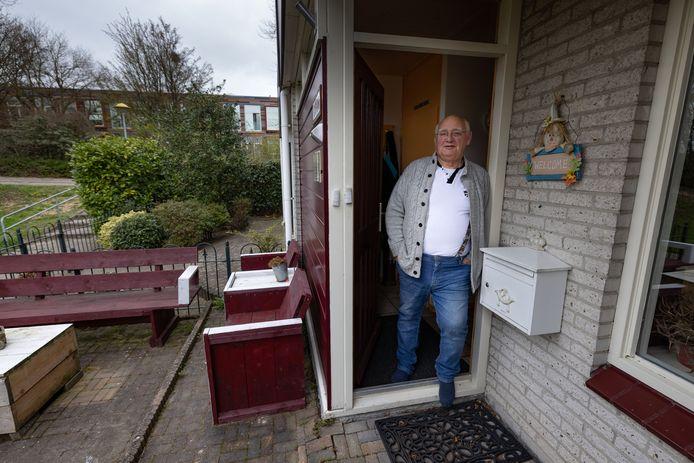 """Buurtbewoner Adri Onderwater in de deuropening van zijn huis. Links op de achtergrond het complex van Iriszorg. ,,Leven en laten leven"""", zegt Onderwater."""