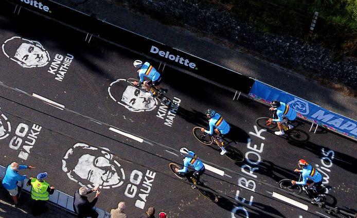 De Belgische ploeg met kopman Wout van Aert fiets over het asfalt op de Smeysberg waar de hoofden van Mathieu van der Poel en Bauke Mollema hen 'aankijken'.