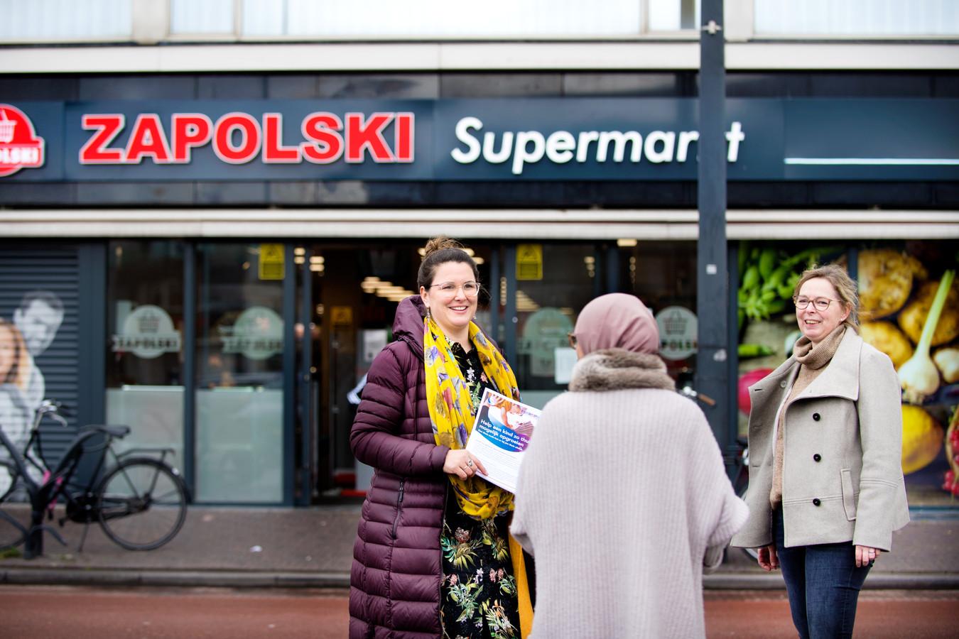 Projectleider Sanne Campfens (links) van Omnia Jeugdzorg en Rowena de Graaff van Combinatie Jeugdzorg delen flyers over het project uit de op Kruisstraat in Eindhoven.