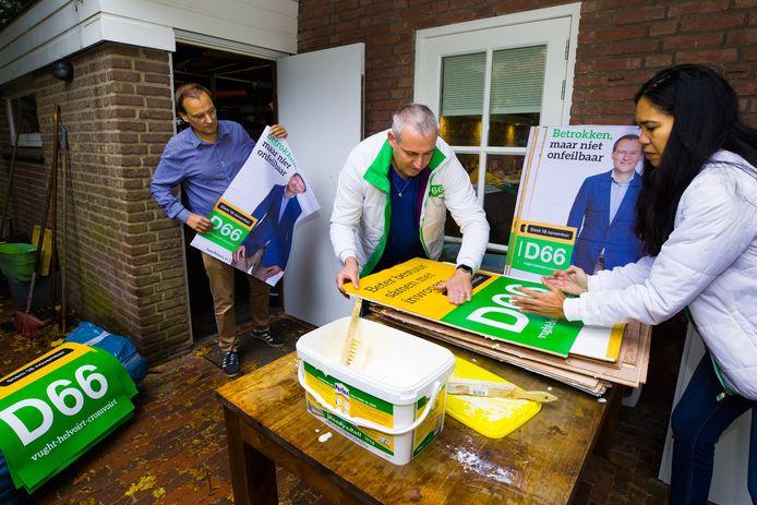 De posters van D66 lijstrekker Fons Potters worden opgeplakt door Joris Vrensen en Naomi Jessurun.