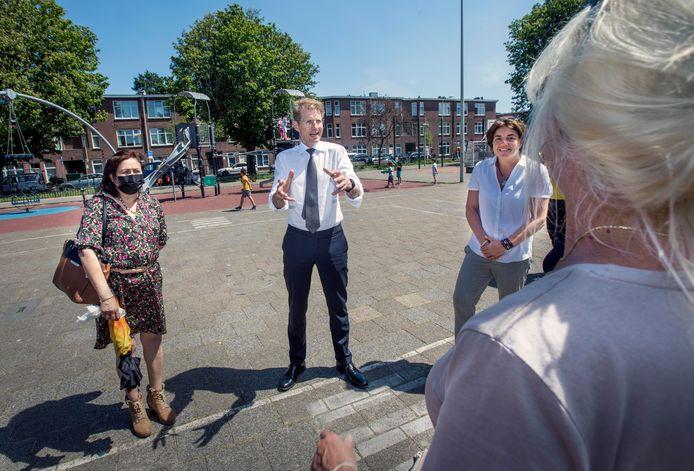 Minister Sander Dekker (midden) praat met bewoners van het Kaapseplein in Den Haag.