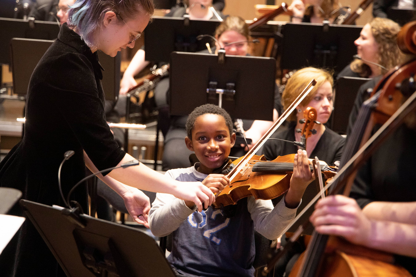 Een Nijmeegse scholier mag de viool uitproberen van een lid van het Nijmeegs studentenorkest.