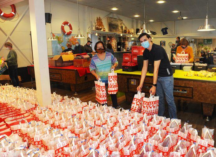 Kersttassen vullen in het zeemanshuis in Vlissingen-Oost. Links vrijwilligers Saskia Martherus en Max Tabak (rechts).