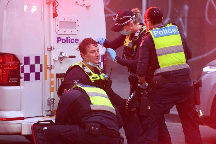 Un agent de police reçoit un traitement lors d'une manifestation de travailleurs de la construction et de manifestants contre la réglementation Covid-19 à Melbourne, le 21 septembre 2021.