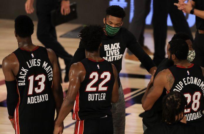 Giannis Antetokounmpo, die niet mee kon doen, feliciteert Jimmy Butler van Miami Heat.