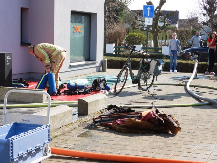 De brandweer bestrijdt een woningbrand in de Baron van Caloenlaan De Haan. Verbrande spullen werden buiten gehaald.
