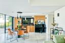 Design in de eetkamer:stoelen van Arper, een tafel van Moooi enlampen van Tom Dixon.Een leukcontrast met de keuken in grenenhout.