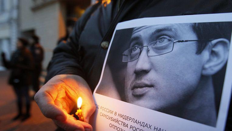 Een man herdenkt de Russische asielzoeker Aleksandr Dolmatov. Beeld EPA
