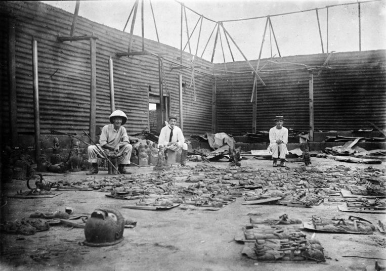 1897: Members of the British punitive expedition surrounded by bronzes, in the burnt down palace of the oba (king) of the Benin Empire. The bronzes were taken as loot, and shipped to collectors and museums all over the world. Beeld -