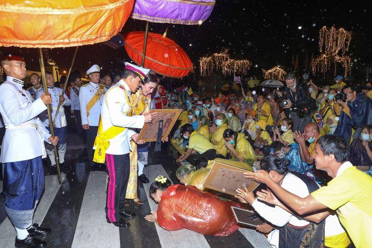 De Thaise koning Maha Vajiralongkorn, koningin Suthida en prins Dipangkorn Rasmijoti begroeten mensen buiten het Grand Palance na een ceremonie voor de vierde herdenking van de sterfdag van koning Bhumibol Adulyadej. Beeld AFP