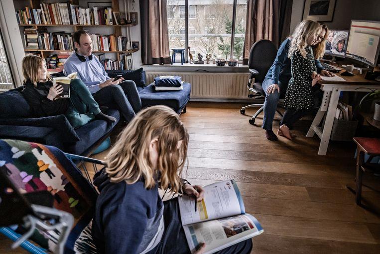 Ouders werken vanuit huis terwijl hun drie kinderen ook thuis onderwijs krijgen in verband met de coronamaatregelen. Beeld Joris van Gennip