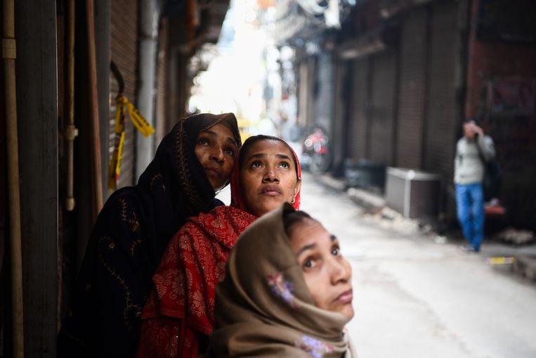 Vrouwen kijken naar de fabriek waar een dag eerder brand uitbrak en 43 arbeiders om het leven kwamen. Beeld AFP