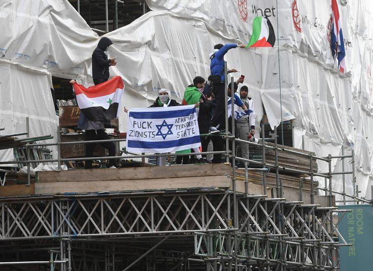 Enkele pro-Palestijnse demonstranten beklimmen een stelling bij de Israëlische ambassade in Londen. Beeld EPA