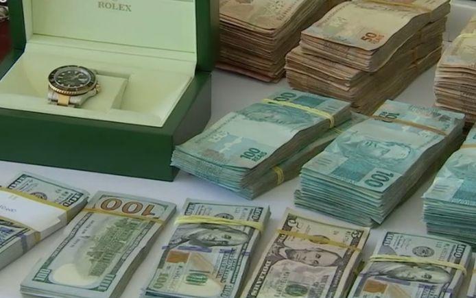 Een van de in beslag genomen Rolex-horloges en cash geld.