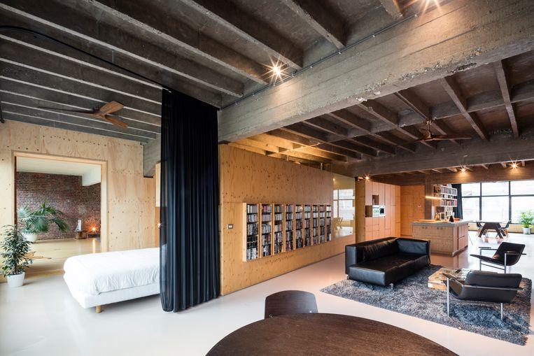 De salontafel in sloophout is onmiskenbaar van de Nederlandse designer Piet Hein Eek. Maar ook de slanke lamp boven het keukeneiland en de onopvallende spots zijn van zijn hand. © Tim Van de Velde Beeld null