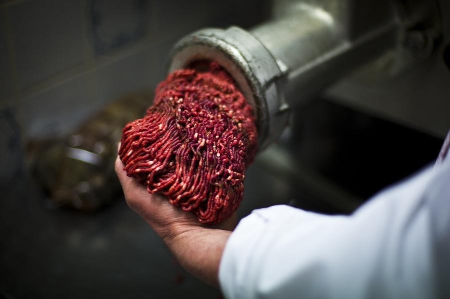 Een slager draait gehakt.