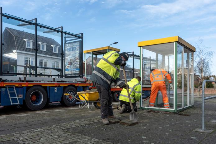 Dennis de Wit verwijdert stoeptegels uit het oude bushokje aan de Damstraat in Yerseke. Op de vrachtauto staat de nieuwe abri al klaar.