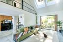 Door de zetel in de lengte te plaatsen, wordt de zithoek bij de rest van de leefruimte betrokken. De tapijten zijn van Ikea.