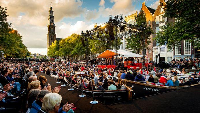 Boten liggen zij aan zij tijdens het jaarlijkse Prinsengrachtconcert in Amsterdam. Het publiek volgt vanaf de boten en pontons in de gracht een optredens van muzikanten.