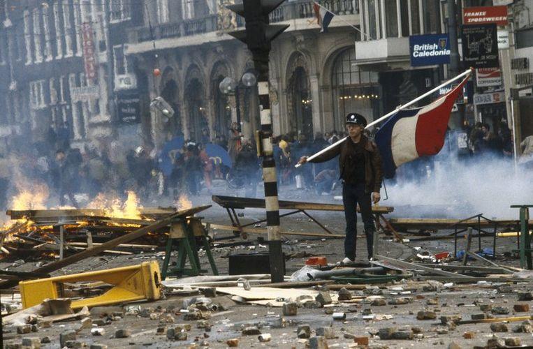 Een kraker staat met een vlag temidden van een enorme ravage op straat tijdens de rellen bij de inhuldiging van koningin Beatrix. De kraakbeweging greep de kroning aan om te protesteren tegen het woningbeleid van de gemeenste Amsterdam, onder het motto 'Geen woning geen kroning'. Foto ANP<br /> Beeld