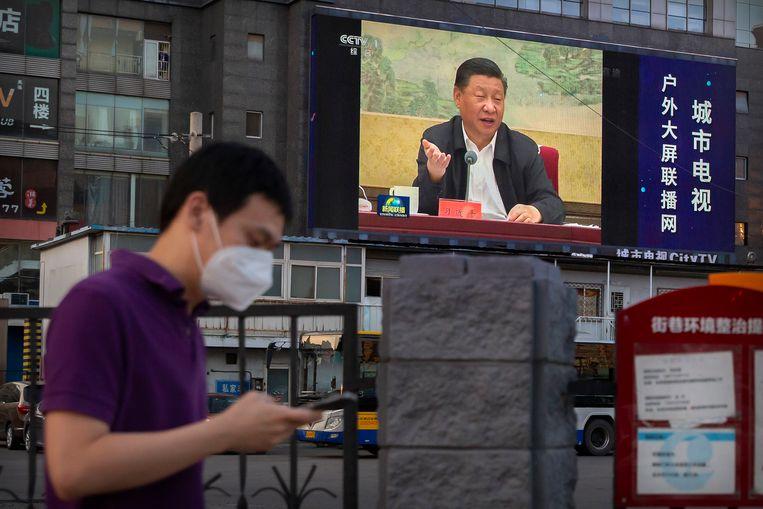 Chinees president aan  het woord op een scherm in de straten van Peking. Volgens Trump is de WHO veel te 'dankbaar' naar China toe. Maar dat is ergens begrijpelijk. Ze moest China aan tafel houden, want ze wilde onder meer zo snel mogelijk de genetische informatie van het virus krijgen. Beeld AP