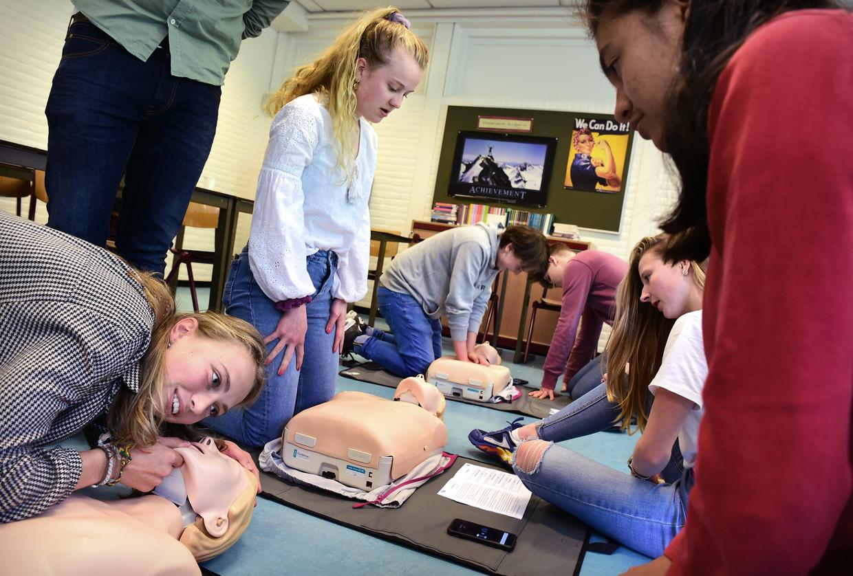 Leerlingen van het Goois Lyceum in Bussum oefenen reanimatie met de AED (Automatische Externe Defibrillator), een draagbaar apparaat dat wordt gebruikt bij acuut hartfalen. Beeld Foto Marcel van den Bergh / de Volkskrant