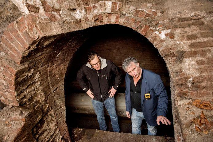 Erfgoedmedewerker Diewert Berben (links) en opzichter Jan van Groesen (rechts) bestuderen in het riool het voegwerk van de historische toegang.