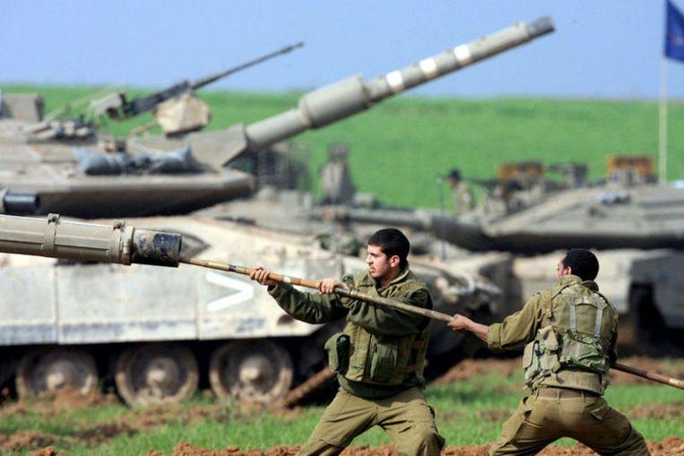 Israëlische soldaten reinigen de loop van een tank nabij de grens van de Gazastrook. Ook woensdag weer werden Hamas-doelen gebombardeerd. Foto EPA/Pavel Wolberg Beeld