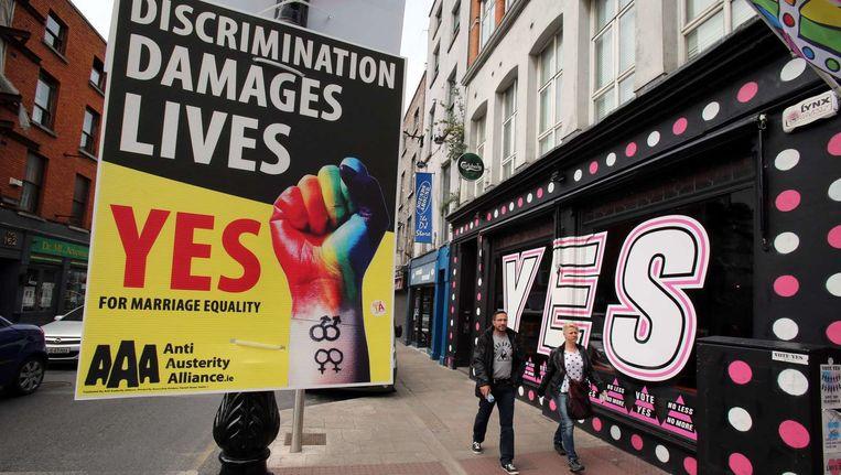Voetgangers in Dublin lopen langs een muurtekening voor het homohuwelijk. Beeld ANP