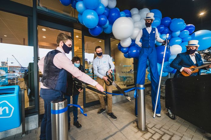 Ondernemer Gianni, de eerste klant en supermarktmanager Niek openen de nieuwe vestiging van Albert Heijn in Ninove.