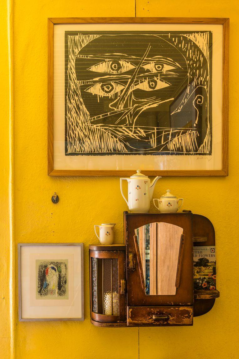Boven het antieke medicijnkastje hangt een houtsnede van Pierre Alechinsky, links een steendruk van Marc Chagall.  Beeld Luc Roymans