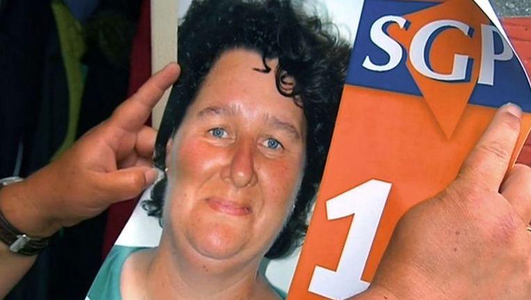 Fragment uit De Vijfde Dag: kandidaat-lijsttrekker Lilian Janse toont haar verkiezingsposter. Beeld EO