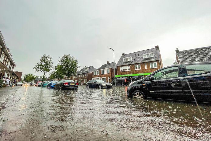 Op de Tongelresestraat staat het water zo hoog dat het bij een kapperszaak naar binnen liep.